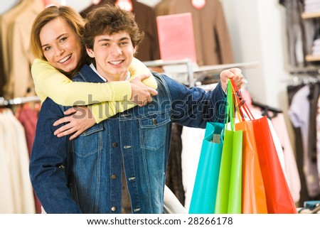 Attractive woman embracing her boyfriend with colorful paperbags in shop - stock photo
