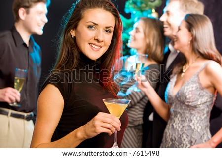 Attractive woman enjoying a cocktail while a party - stock photo
