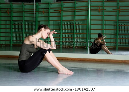 Attractive woman exercising at dance hall - stock photo