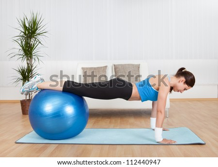 Attractive Woman Exercising With Exercise Ball At Home. - stock photo