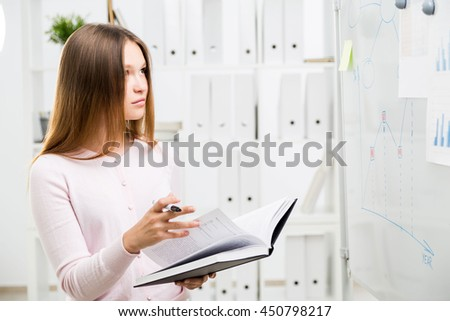 Attractive woman flipping through book and looking at office whiteboard with business charts and graphs - stock photo