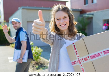 Attractive woman happy after being delivered a parcel - stock photo
