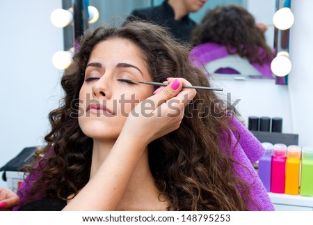 attractive woman having mascara make up applying in salon - stock photo