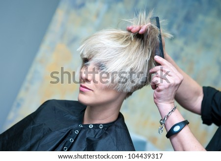 attractive woman having new hairstyle in salon - stock photo
