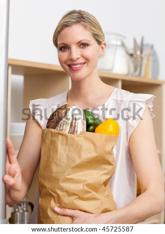 Attractive woman holding a grocery bag in the kitchen - stock photo
