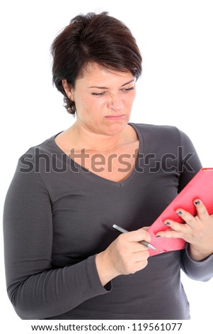 Attractive woman holding a red folder in her hands grimacing in disgust at what she is reading isolated on white - stock photo