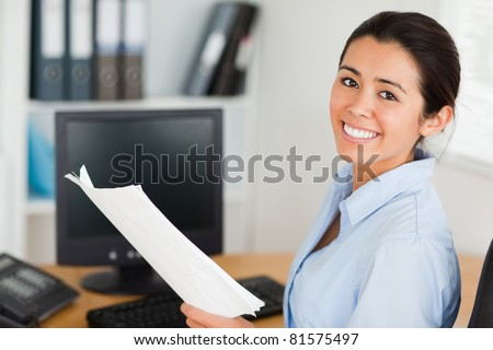 Attractive woman holding a sheet of paper and posing while sitting at the office - stock photo