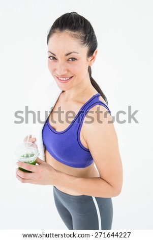 Attractive woman holding green juice on white background - stock photo