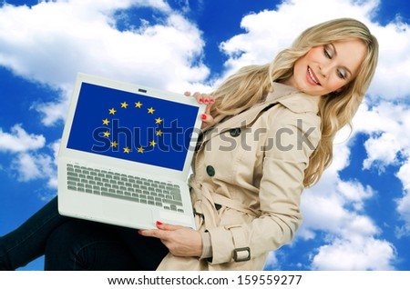attractive woman holding laptop with european union flag on the screen - stock photo