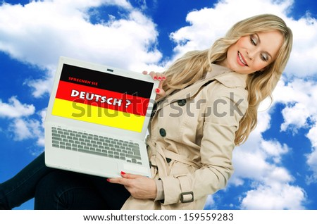 attractive woman holding laptop with german language sign on the screen - stock photo