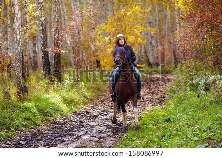 attractive woman in a hat riding a horse through the forest road - stock photo