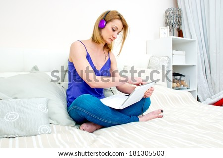 attractive woman in bed with laptop computer and headphones - stock photo