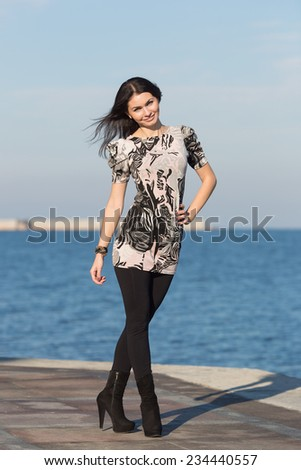 Attractive woman in black trousers on open air. Cute business woman walks along seafront - stock photo