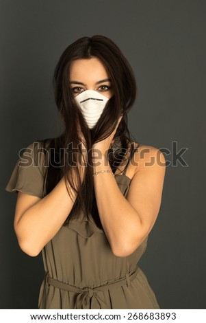 Attractive woman in elegant dress trying to hide her protective mask with her long dark hair, closeup portrait of an interesting Asian - Caucasian mixed woman on dark background. - stock photo