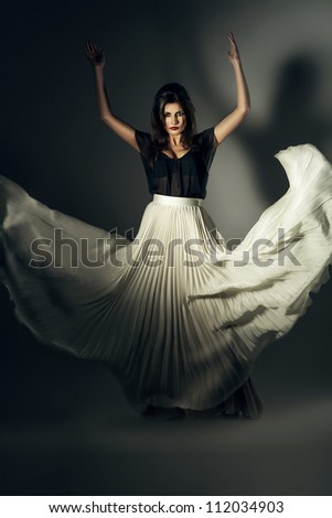 attractive woman in flying long skirt - stock photo