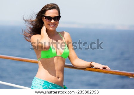 attractive woman in green bikini on a cruise ship - stock photo