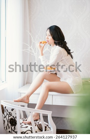 Attractive woman in male shirt eating cake - stock photo