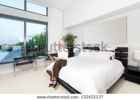 Attractive woman in modern bedroom - stock photo
