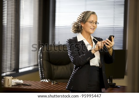Attractive woman in office using cellphone. - stock photo