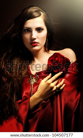 attractive woman in red drapery with red rose - stock photo