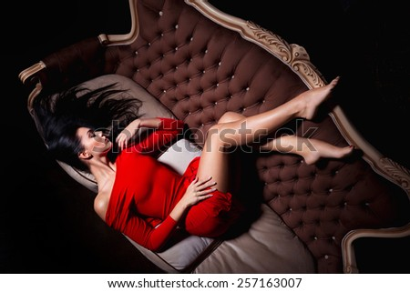 Attractive woman in red dress posing in a sexy way - stock photo