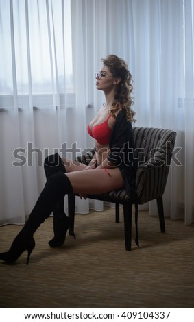 Attractive woman in red lingerie posing sitting on armchair with white curtains on background. Portrait of sensual perfect legs girl with long black stockings. Sexy female with long curly hair indoor - stock photo