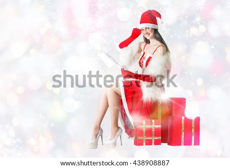 Attractive woman in Santa Clause outfit  reading letter to Santa. . Christmas background - stock photo