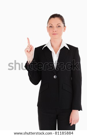 Attractive woman in suit pointing at a copy space while standing against a white background - stock photo