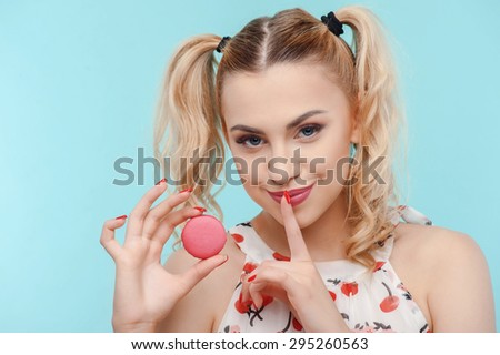 Attractive woman is holding brownie with appetite. She is raising her finger to her lips. The lady is asking to keep her secret and smiling slyly.  Isolated on blue background - stock photo