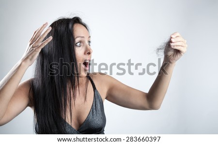 Attractive woman is looking shocked to her lost hair - stock photo