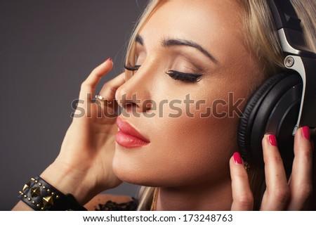 Attractive woman listening music through headphones, eyes closed.  - stock photo