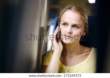 Attractive woman listening to a call on her mobile phone looking into the distance with a thoughtful expression while travelling by train - stock photo