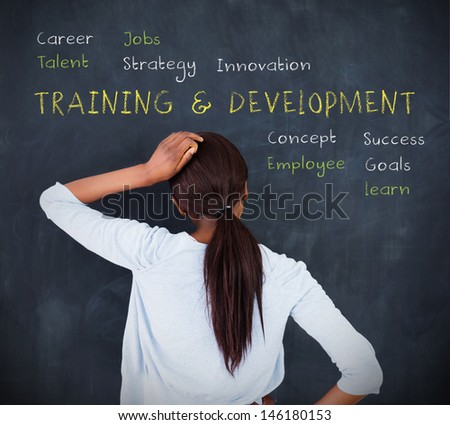 Attractive woman looking at a chalkboard with business terms written on it - stock photo