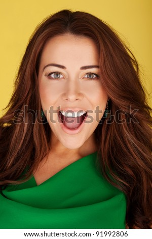 Attractive woman looking at the camera in amazement and awe with mouth open and animated expression. - stock photo