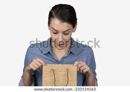 Attractive woman looking into a brown paper bag - stock photo
