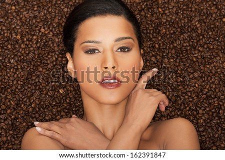 Attractive woman lying in coffee grains. Fron view. Closeup. - stock photo