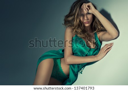 Attractive woman lying on the background in green dress - stock photo
