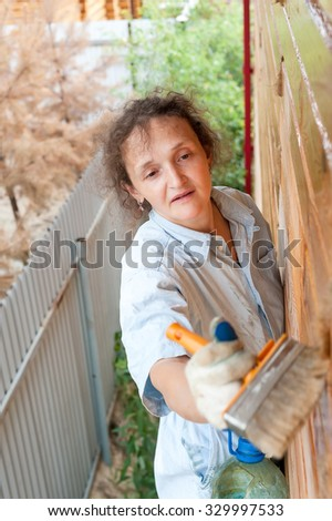 Attractive woman making biochemical impregnation against fire and bugs on own wooden house - stock photo