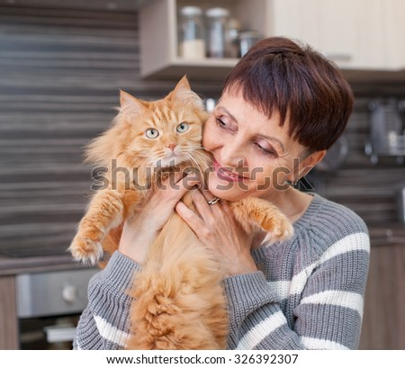 attractive woman of 50 years with a red cat in her arms at home - stock photo