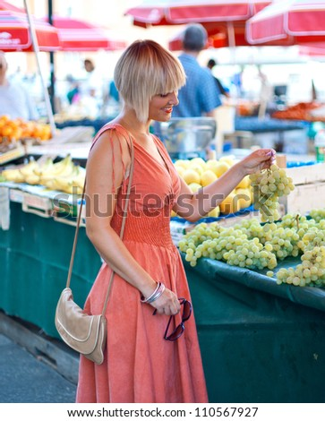 attractive woman on market choosing fruit - stock photo
