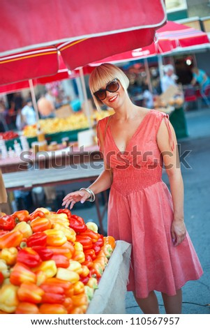 attractive woman on market choosing vegetables - stock photo