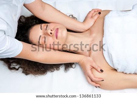 attractive woman on massage table in beauty salon having neck adjustment - stock photo