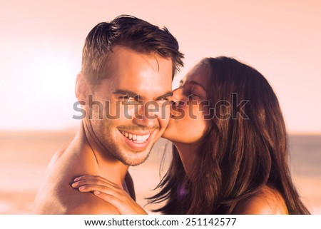 Attractive woman on the beach kissing her boyfriend on the cheek - stock photo