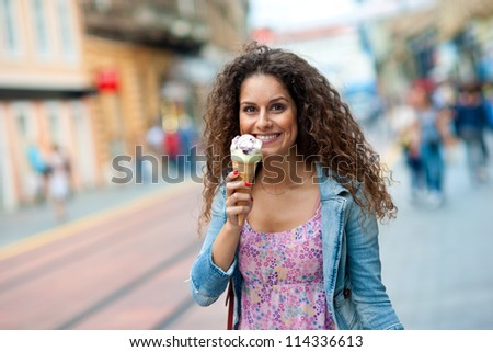 attractive woman on the street having fun and eating ice cream - stock photo