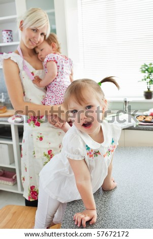Attractive woman playing with her daughters in living room - stock photo