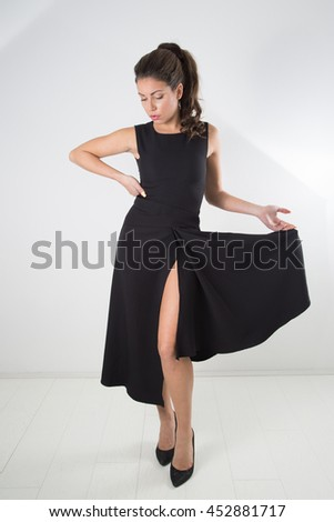 Attractive Woman Posing In Black Elegant Dress And Looking Down, Full-Length Studio Shot Over White Background  - stock photo