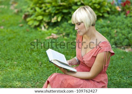 attractive woman reading book in the park - stock photo
