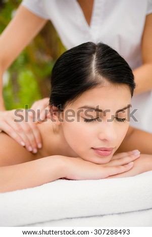 Attractive woman receiving back massage at spa center - stock photo