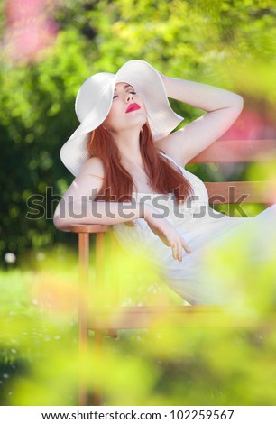 Attractive woman relaxing in a garden - stock photo