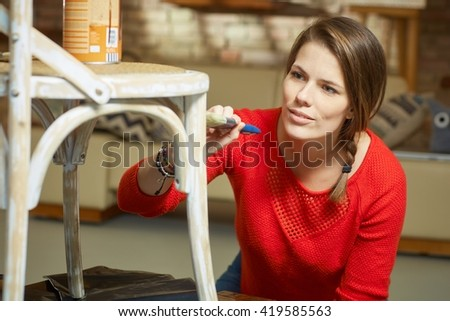 Attractive woman renewing, painting chair at home. - stock photo